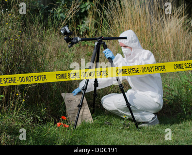 Forensic scientist checking for evidence behind a crime scene barrier - Stock Photo