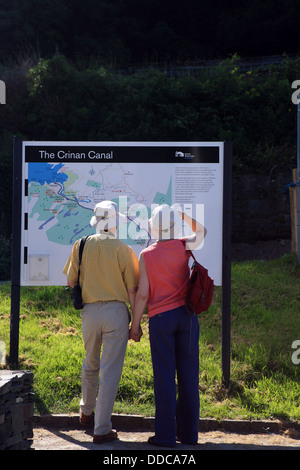 Couple holding hands and looking at the Crinan Canal information board at Crinan in Scotland - Stock Photo