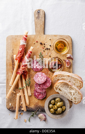 Bread sticks with ham and salami on wooden background - Stock Photo