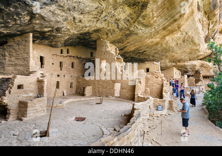 Tourists at Spruce Tree House ruins, ancient Anasazi pueblo dwellings, Mesa Verde National Park, Cortez, USA - Stock Photo