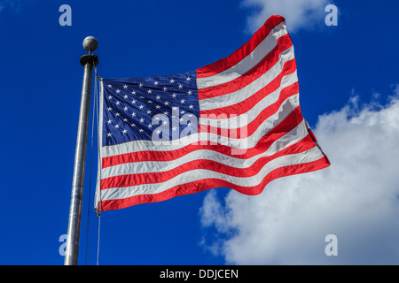 A photograph of an American flag blowing in the breeze against a very blue sky with some contrasting clouds - Stock Photo