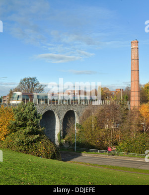 Luas crosses the 9 Arch viaduct in Milltown, Dublin with chimney in picture - Stock Photo