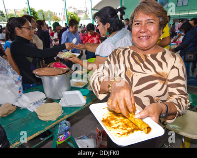 Women preparing mole enchiladas at a food stall during a gastronomical festival in Puebla, Mexico. - Stock Photo