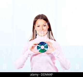 Brunette woman holding cd disk - Stock Photo