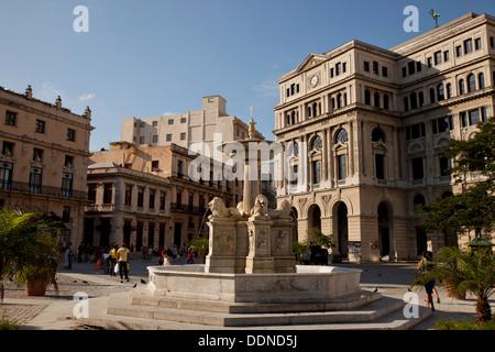 marble fountain Fuente de los Leones and Havana Stock Exchange / Lonja del Comercio building on Plaza de San Francisco - Stock Photo