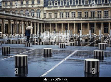 Man with an umbrella walking in the rain through Les Colonnes de Buren. Conseil d´état, Palais Royal, Paris, France - Stock Photo
