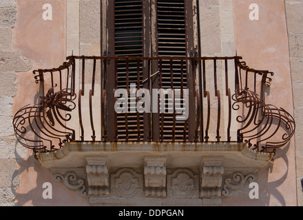 A traditional curved iron balcony railing in front of a window in Ortigia, Syracuse, Sicily, Italy - Stock Photo