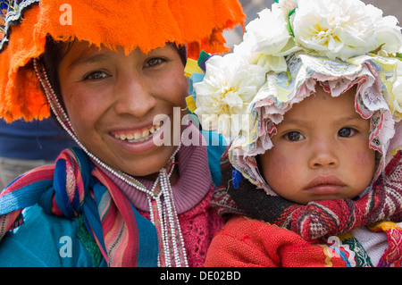 Woman and her daughter wearing traditional Andean bonnets, Pisac Market, Sacred Valley of the Incas, near Cusco, - Stock Photo