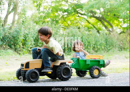 Young brother and sister riding on toy tractor - Stock Photo