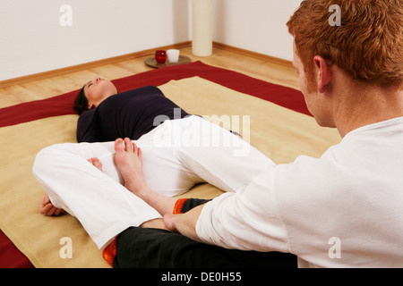 Young woman doing relaxation exercises with a Qigong coach - Stock Photo