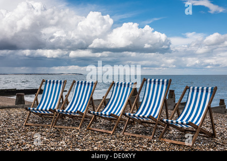 Blue & White Striped DeckChairs on the Beach, Whitstable, Kent, UK. - Stock Photo