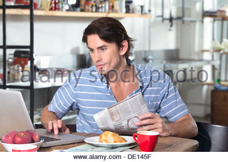 Man with newspaper using laptop at kitchen table - Stock Photo