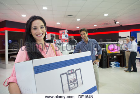 Portrait of smiling woman holding box in electronics store - Stock Photo