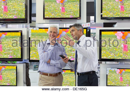 Flat screen televisions behind salesman and senior man in electronics store - Stock Photo