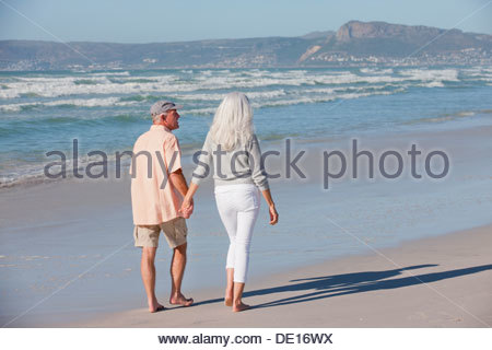 Senior couple holding hands and walking on sunny beach - Stock Photo