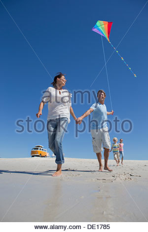 Family with kite running on sunny beach with van in background - Stock Photo
