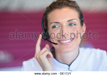 Close up of smiling beautician talking on the phone with headset - Stock Photo