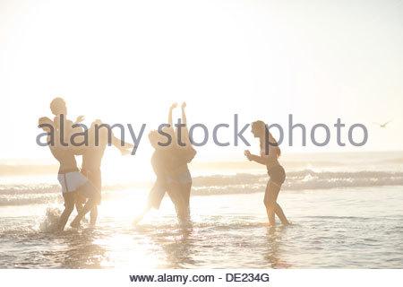 Friends in swimsuits walking on beach - Stock Photo