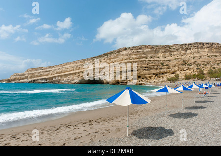 Neolithic cave dwellings in the yellow sandstone, parasols on the beach of Matala, former site of the hippies, Crete, - Stock Photo