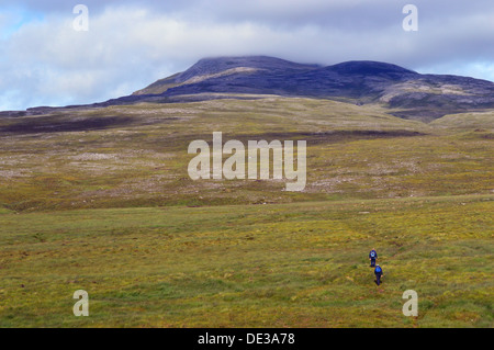Two male walkers at the start of the climb towards the Scottish mountain Canisp (a Corbett) from Loch Awe. - Stock Photo