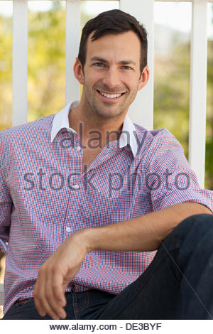 Smiling man having cup of coffee outdoors - Stock Photo