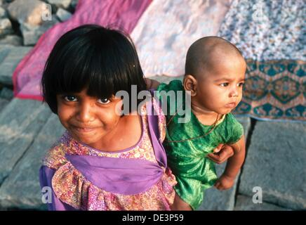 Indian girl with baby on her looks with big eyes - Stock Photo