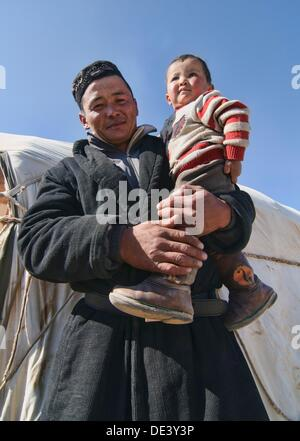 portrait of a Kazakh eagle hunter and his son in the Altai Region of Bayan-Ölgii in Western Mongolia - Stock Photo