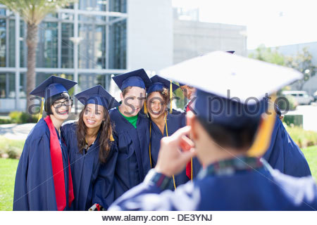 Graduate taking photograph - Stock Photo