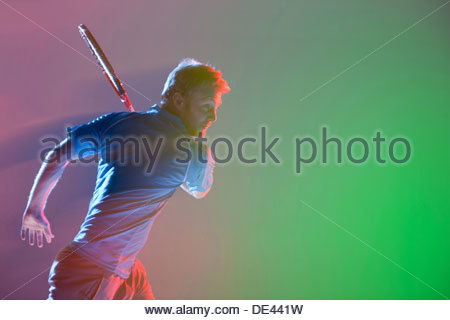 Tennis player swinging racket - Stock Photo