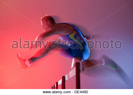 Blurred view of athlete jumping hurdles - Stock Photo