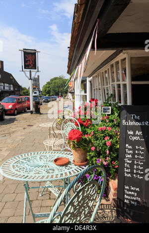 Chairs, tables and flowers outside The Bakehouse cafe teashop on the main street in Biddenden, Kent, England, UK, - Stock Photo