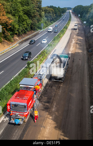 Roadworks, on Autobahn A52, Essen, Germany.  Removal of the asphalt surface with a cutter, then new, porous asphalt - Stock Photo