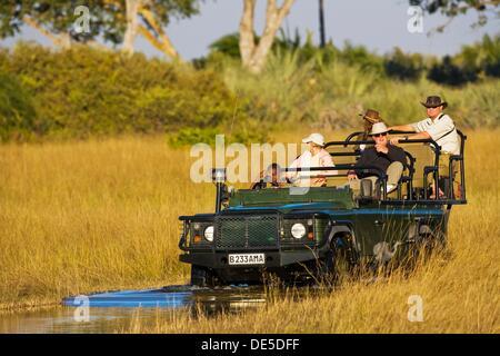A safari vehicle with tourists driving through the Okavango Delta in Botswana, Africa - Stock Photo