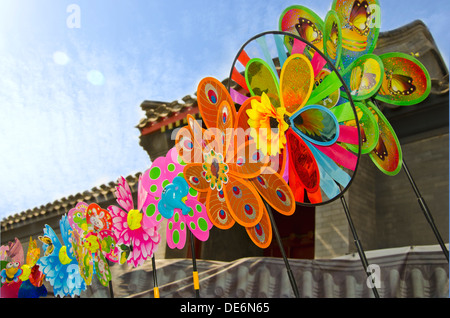 a set of multicolored pinwheels agains chinese houses and blue sky - Stock Photo