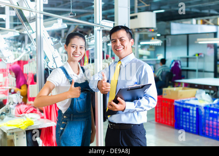 Indonesian Seamstress is new assigned in a textile factory, the foreman gives her training for the new job - Stock Photo