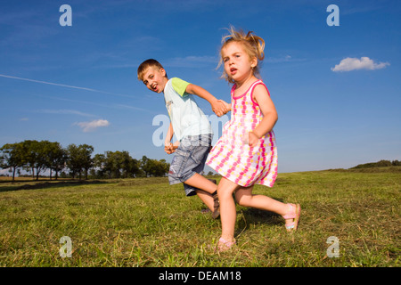 Little girl, 3 years, and her brother, 7 years, outdoors - Stock Photo