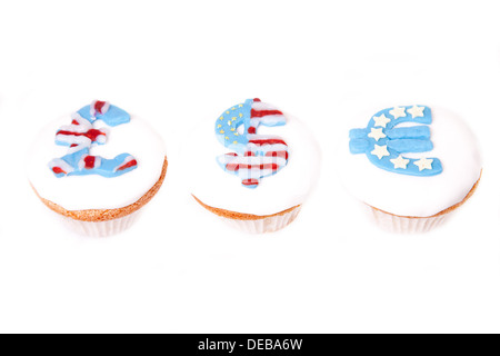 pound, dollar and euro signs on cup cakes on white background. - Stock Photo
