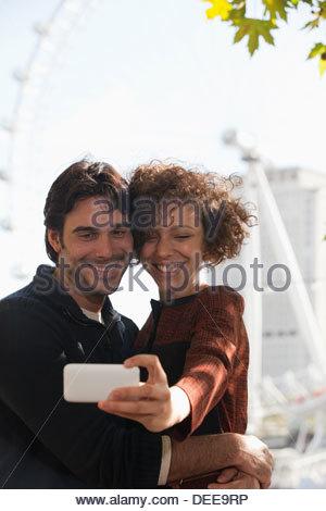 Couple taking self-portrait with digital camera below ferris wheel - Stock Photo