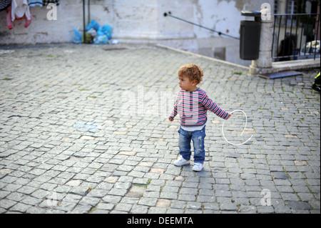 A local boy in stripe sweater plays in Alfama, Lisbon, Portugal. - Stock Photo