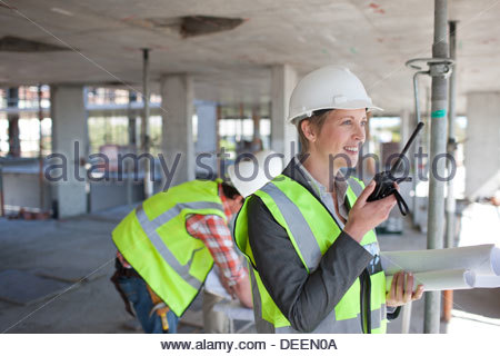 Businesswoman talking on walkie talkie on construction site - Stock Photo