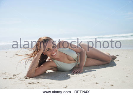 Woman in bathing suit laying on beach - Stock Photo