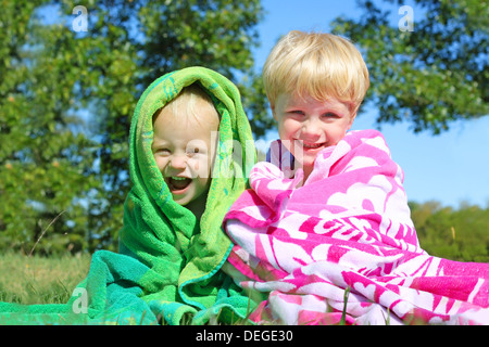 Two happy young children; a little boy and his baby brother are smiling as the sit wrapped together in colorful - Stock Photo