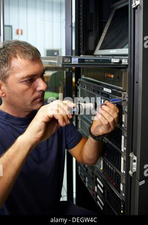 Man using screwdriver, compute cluster maintenance - Stock Photo