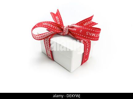 A wrapped Christmas present with a colourful red ribbon bow on a white background. - Stock Photo