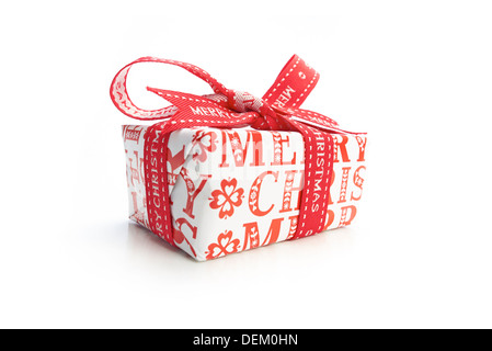 A wrapped Christmas present with a colourful ribbon bow on a white background. - Stock Photo