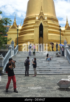 Tourists take photos at the golden Phra Si Rattana Chedi at the Grand Palace complex in Bangkok - Stock Photo