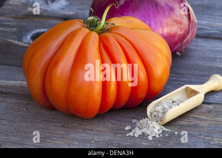 Coeur de Boeuf Tomato and a whole red Onion with Basil Sea Salt in a wooden Spice Scoop on a old wooden Table - Stock Photo