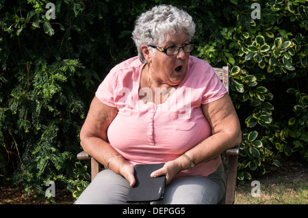A shocked old / elderly / senior lady (aged 76) sitting in a chair in her garden. - Stock Photo