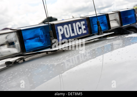Blue & clear flashing light array with communication aerials on a the roof of a British police car - Stock Photo