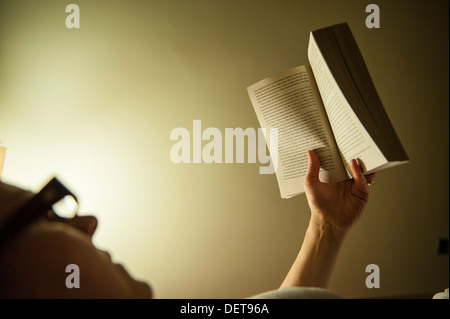 A woman reads in bed at night - Stock Photo